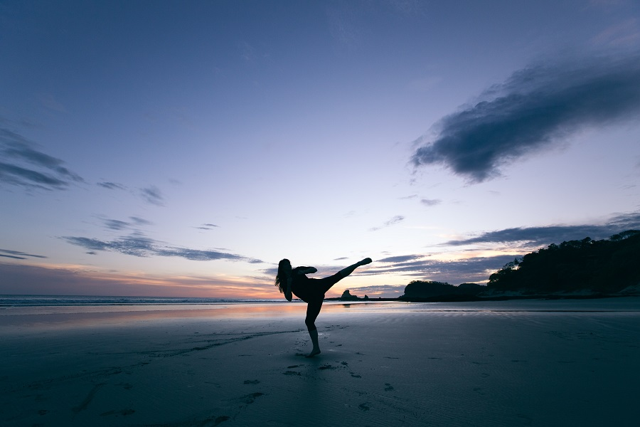 Adult practices karate on the beach