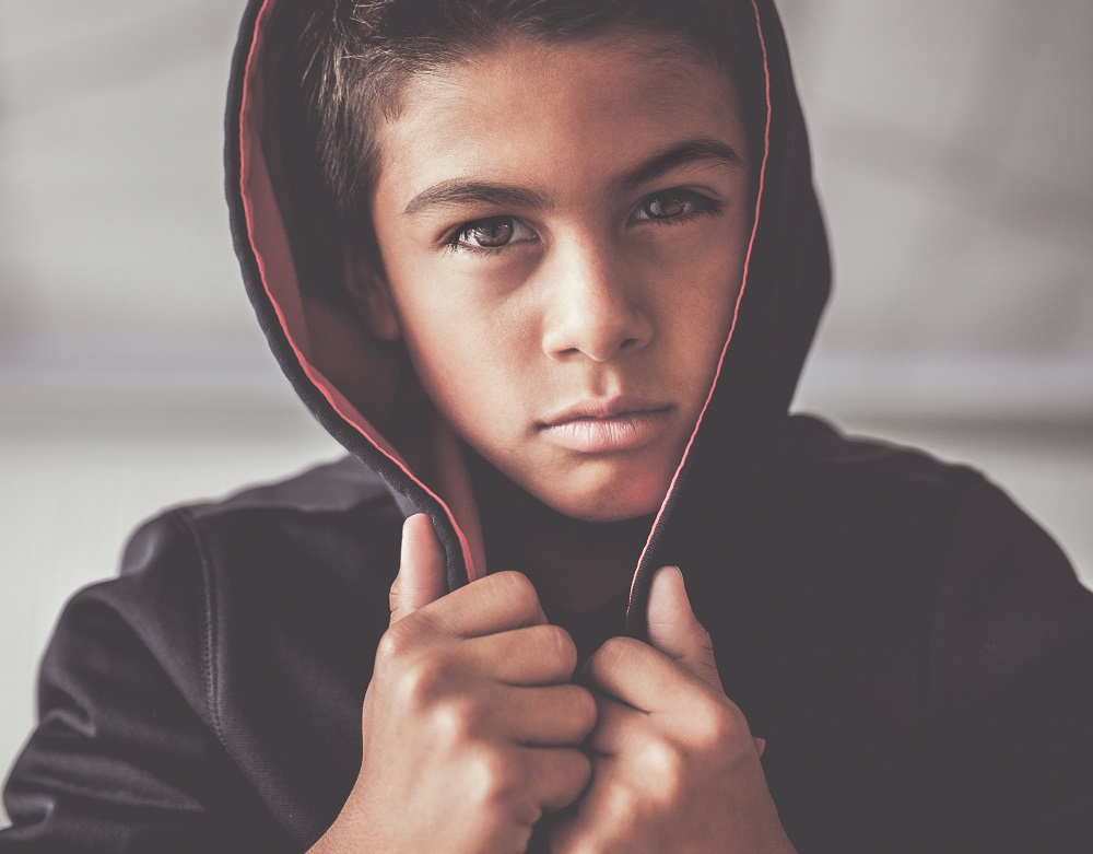 young boy stares intensely at the camera while wearing a hoodie