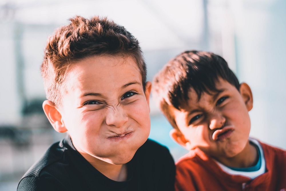 Two young boys make silly faces at the camera