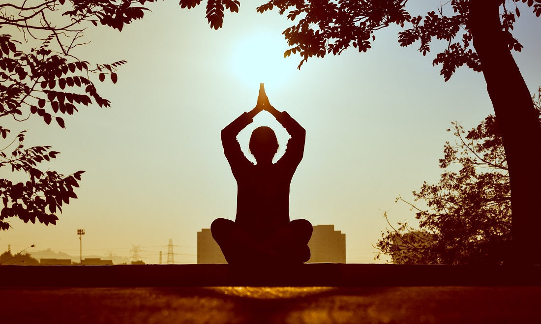 silhouette of older child in a meditation pose outdoors