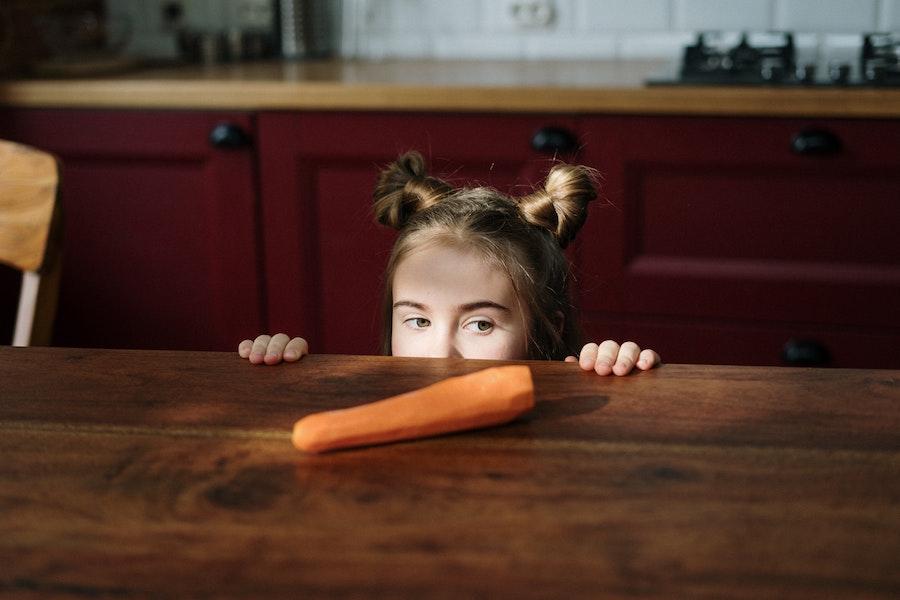 girl-peeking-over-on-brown-wooden-table